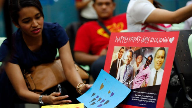 Relatives of Malaysian passengers on board the missing Malaysia Airlines Flight 370 looks at a picture of missing crew during an event to commemorate the 100th day after the flight went missing, in Kuala Lumpur, on June 15.