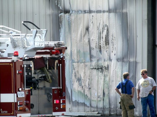 Emergency personnel examine the scene after quickly extinguishing a fire in a hangar at Murfreesboro Municipal Airport on, Friday morning August  22, 2014.