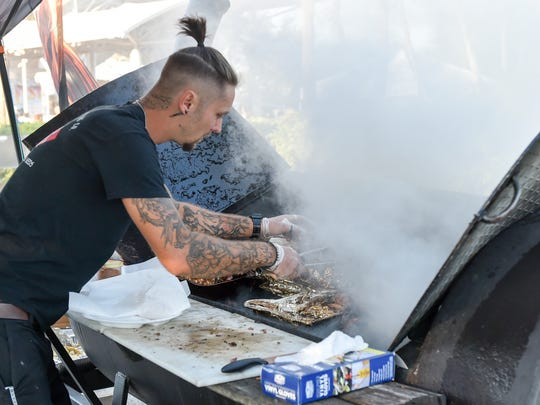Cory Lach of Simply Southern Catering Co. checks on his mouth watering chicken and pork during the Bonita Blues Festival held at Riverside Park in Bonita Springs, Friday March 9.