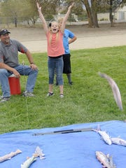 Fernley Intermediate School sixth-grader Ashlyn Bertok tosses a fish back after mock-fly fishing at the carnival.