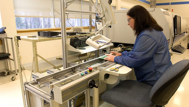 General Electric worker Sheree Trejo inspects a printed circuit board just off a new automated line at the company's plant at the Rochester Science Park in 2010.