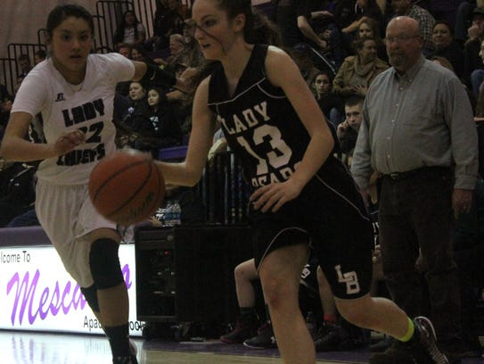 Makayla Moberly, right, drives past Justice Blake on