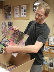 Record Collector owner Kirk Walther opens a box of
