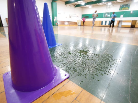Dennis Walcott, East Ramapo school district monitor along with Jacqueline Polanco, principal of the East Ramapo Early Childhood Center in Spring Valley look over one of several leaks that are impacting both of the school's gym on Sept. 30, 2015.