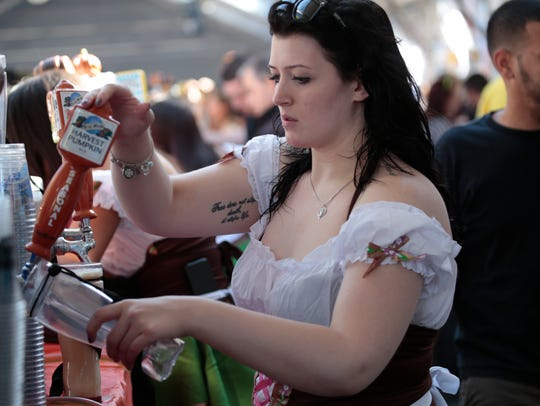 Bartenders fill pints of beer at the White Plains Octoberfest