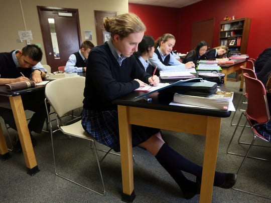Natalie Monson, 15, a sophomore at Tall Oaks Classical School near New Castle, studies during Christian theology class.