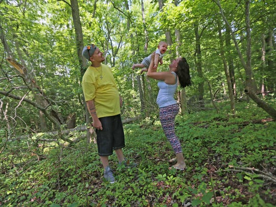 31 year-old Brian Laurenzi watches his 5 month-old son Braylen fly through the air in his girlfriend Amanda Lofland hands while revisiting the wooded area the couple once lived in while getting clean from heroin.