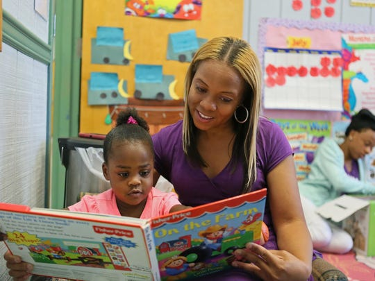2 year-old Emari Holmes reads a book with owner of Our Future Christian Childcare Center Jacqueline Harris while she stopped to visit a class.