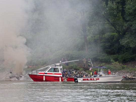 Firefighters work on put out a boat fire on the C&D Canal near Del. 1.