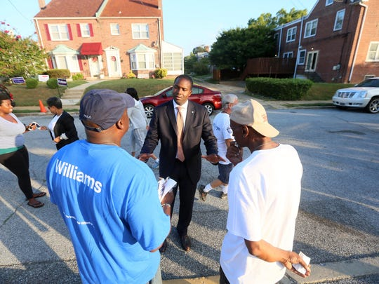 Wilmington mayor candidate Eugene Young speaks with supporters outside Harlan Elementary School Tuesday morning. Young faced a crowded field in the primary.