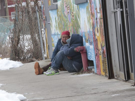 A pair of men, one fast asleep on the sidewalk in Spring Valley on Jan. 24, 2016.  Various homeless organizations are doing a point in time count survey to document how many homeless people live on the streets throughout Rockland County .