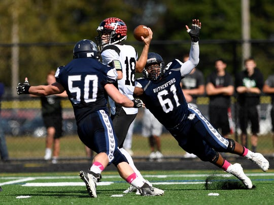 Rutherford's Vincent Nikolic #50 and Lawson Fisher #61 put pressure on Manchester quarterback Antonio Bisciotti #18. Rutherford defeated Manchester 28-0 on Saturday, October 21, 2017 in Rutherford, NJ.
