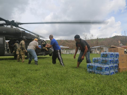 U.S. Soldiers, assigned to 101st Combat Aviation Brigade (CAB), 101st Airborne Division (Air Assault), work with the locals to unload food and water from a HH-60 Black Hawk helicopter with the help from locals in order to help with the Hurricane Maria disaster, Puerto Rico, Oct. 5, 2017. The 101st Combat Aviation Brigade responded to Hurricane Maria in an attempt to provide relief to the people of Puerto Rico after the natural disaster struck.