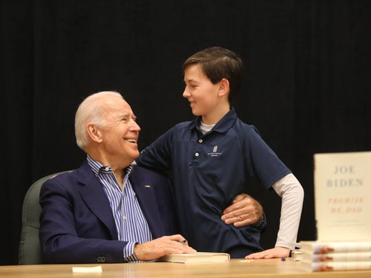 Former Vice President Joe Biden holds 13 year-old Teyton Pressley, a brain tumor survivor, in his arms before autographing his new book, Promise Me, Dad: A Year of Hope, Hardship, and Purpose, for Pressley.