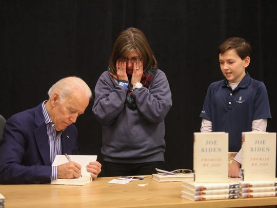 Former Vice President Joe Biden autographs Christina Pressley's copy of his new book,  Promise Me, Dad: A Year of Hope, Hardship, and Purpose, as she wipes away tears with her 13 year-old son Teyton Pressley, a brain tumor survivor, by her side on Thursday morning.