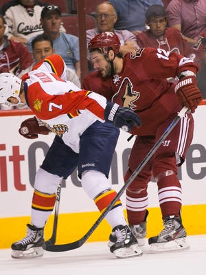 Coyotes' Justin Hodgman and Panthers' Dmitry Kulikov fight for the puck in the first period at Gila River Arena in Glendale, AZ on Saturday, Oct. 25, 2014.