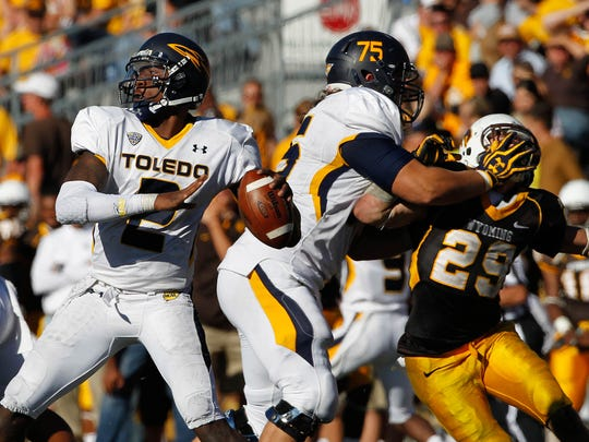 Toledo Rockets quarterback Terrance Owens (2) looks to throw while being protected by teammate Greg Mancz (75) from Wyoming Cowboys safety Luke Ruff (29) during the fourth quarter in a 2012 Toledo win.
