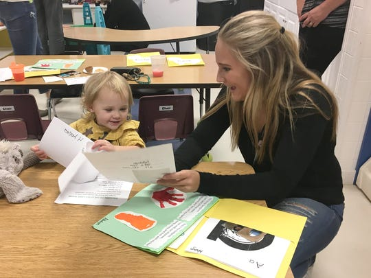 Kennedy Griest checks out daughter Adalyn's schoolwork at Tot Spot Preschool & Child Care in Brighton.