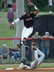 Clinton third baseman Desmyn Baker leaps over a sliding
