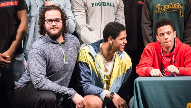 Reynolds high school's Jake Setterlind (left) poses for a photograph with his football teammates during the signing day ceremony, Wednesday, Febnruary 7, 2018.