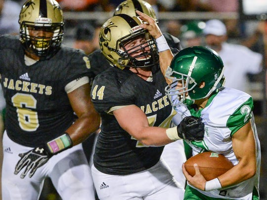 Hanna senior Ryan Smith(44), middle, sacks Easley's Bailey Catoe (2) near teammate Zacch Pickens(6), left, during the second quarter at T.L. Hanna High School in Anderson on Friday.