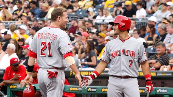 Cincinnati Reds shortstop Eugenio Suarez (7) greets third baseman Todd Frazier (21) after Frazier scored a run against the Pittsburgh Pirates.