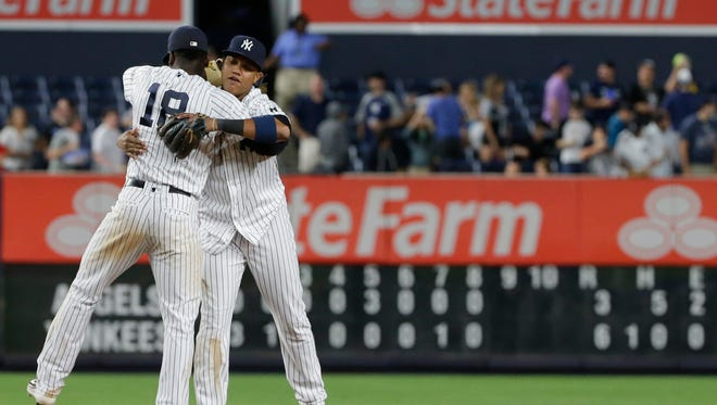 New York Yankees' Didi Gregorius, left, hugs Starlin Castro after the Yankees defeated the Los Angeles Angels 6-3 in a baseball game Tuesday, June 7, 2016, in New York.