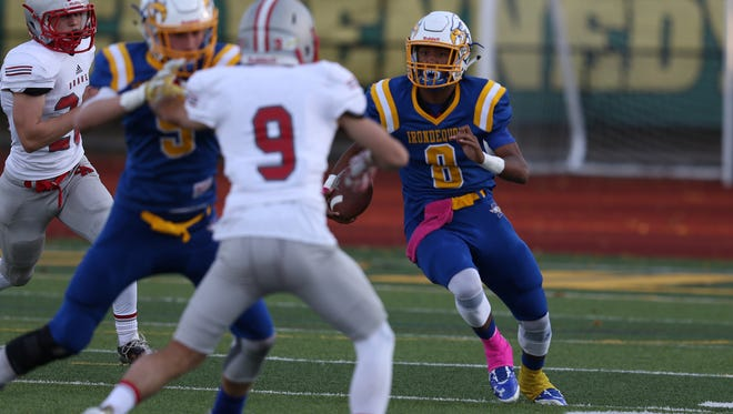 Irondequoit's quarterback Frederick June Jr. looks for an opening to run through while carrying the ball.