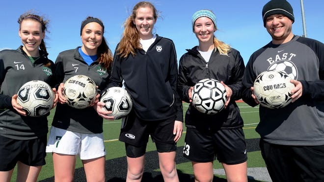Among South Lyon East's key returnees for coach Jon Cadwallader (right) include (from left) Amber Hamers, Lauren Kuznicki, Abby Jones and Paige Green.