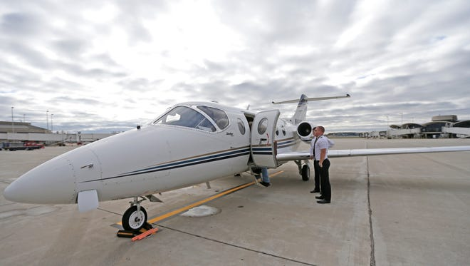 OneJet pilot Brian Wolfe (front) and first officer Ryan Switzer stand outside a OneJet airplane. A media event was held Tuesday at the OneJet terminal at Milwaukee County's Mitchell International Airport to kick off OneJet's new service to Columbus, Ohio, and Omaha, Neb.