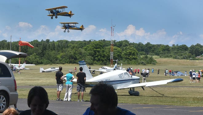 Biplanes, crowds and fish boil diners under the shade of a tree at the annual Washington Island Fly-In Fish Boil on Saturday, July 16, 2016.