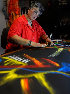 Kateri Pomeroy creates an abstract drawing at Turnip Green Creative Reuse studio. Pomeroy may not have a permanent home, but through her art she feels rooted in a way she has long missed.