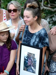 Genna King holds a photo of her brother during the