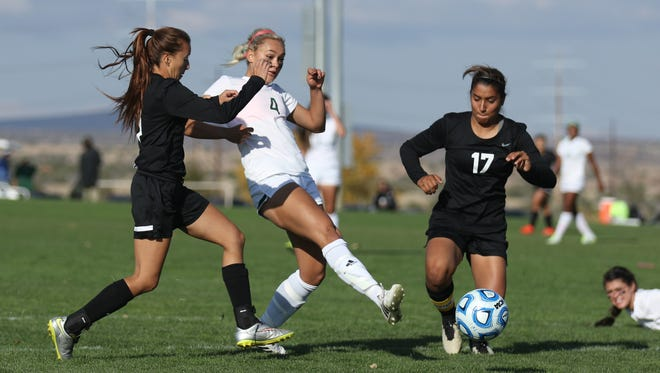 Farmington's Arin Coleman scores a goal between Roswell defenders Jessica Murillo, left, and Viri Campas on Thursday at the Bernalillo Sports Complex.
