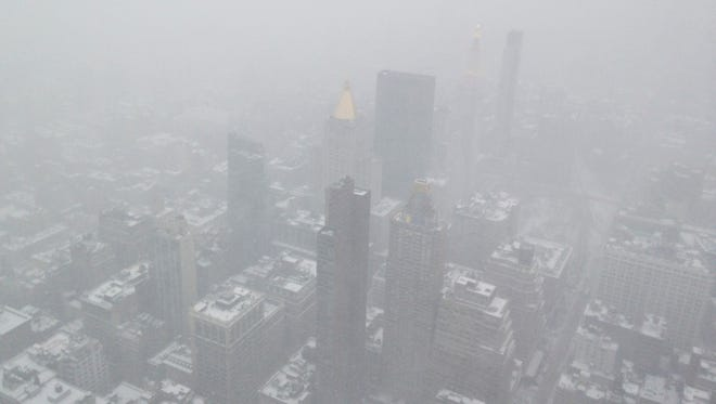 The view from atop the Empire State Building as snow falls on New York City on Monday.