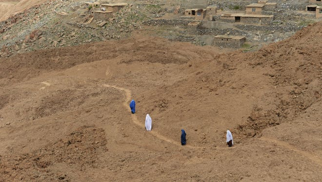 Afghan villagers walk in Aab Bareek village in Argo district of Badakhshan following a landslide in May 2014.
