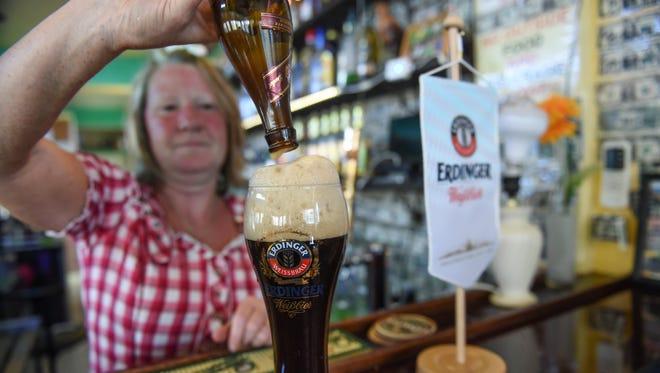 """Ilona Koenig of Mc Kraut's pours a bottle of Erdinger """"Dunkel"""" at Mc Kraut's in Malojloj on Feb. 25."""