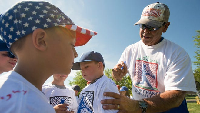 Ernie Romero signs t-shirts for kids participating in the Front Range Baseball Camp at Edora Park on Thursday. Romero has been teaching baseball fundamentals in the program for 30 years.