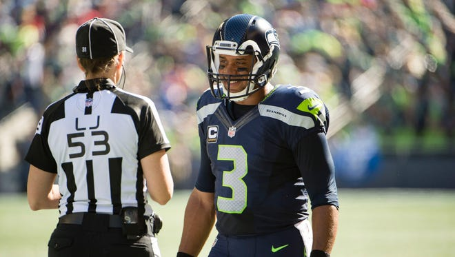 Seattle Seahawks quarterback Russell Wilson (3) talks to line judge Sarah Thomas (53) during a time out in a game against the San Francisco 49ers at CenturyLink Field.