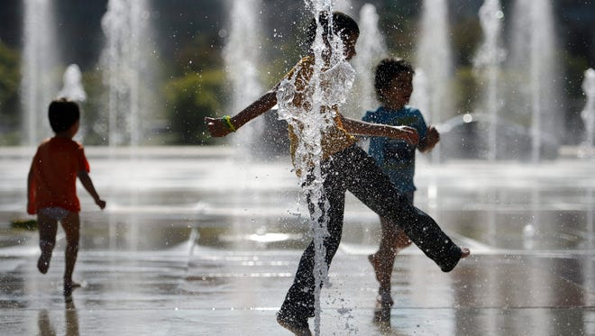 Children play in a fountain on a warm day in Geneva on Sept. 27.