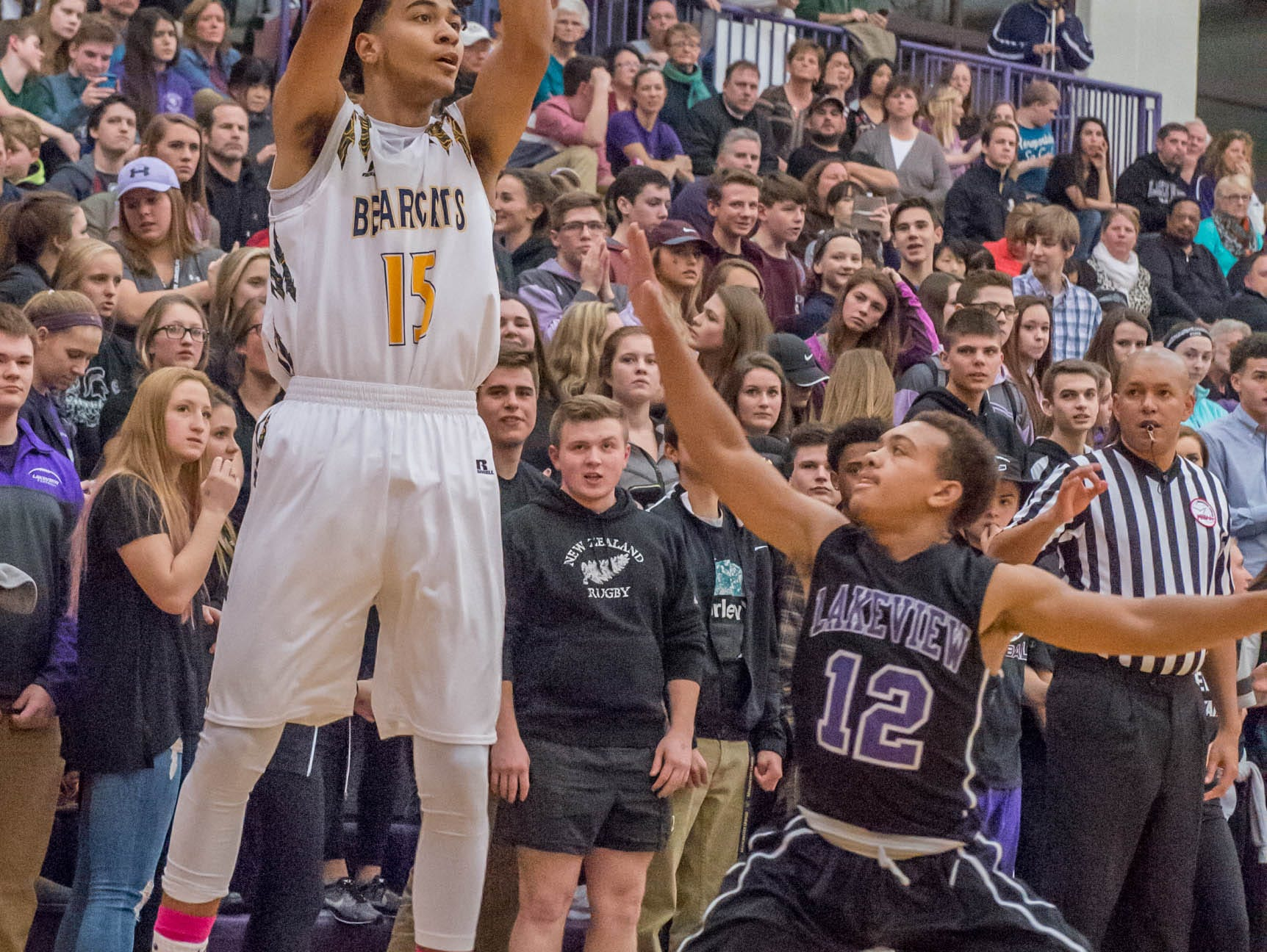 Battle Creek Central's Austin Johnson (15) takes his shot over Lakeview's CJ Foster (12) during Friday evening's game.