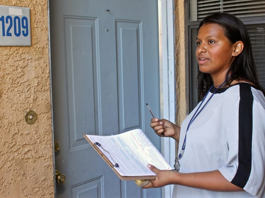Volunteer Summer Rodriguez, a Desert Hot Springs High School student, waits by the front door of a residence in Desert Hot Springs. A group of volunteers knocked on doors Wednesday as they attempted to convince Latinos to register to vote.