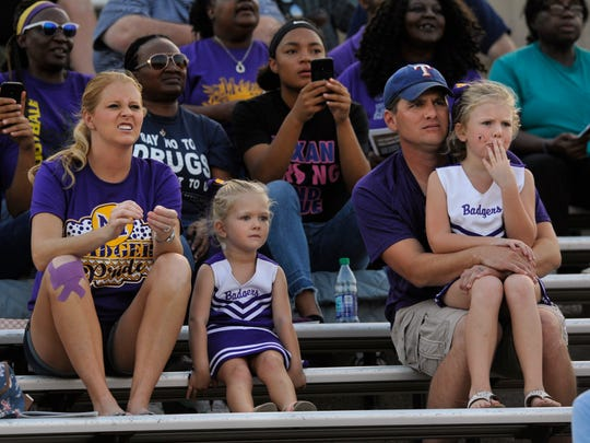 McKinley Crouch, 6, puts her hand to her mouth as she watches the Merkel High School Badgers play against Eastland Thursday August 31, 2017 during the 13th Annual Champions Classic. McKinley and her father Kegan, 3 year-old sister Camdyn, and their mother Cassi were all rooting for the Badgers.