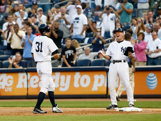 New York Yankees right fielder Ichiro Suzuki reacts with first base coach Mick Kelleher after recording his 4000th hit against the Toronto Blue Jays at Yankee Stadium.<br />