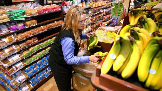 Barb LeBlanc, Kwik Trip store leader, stocks bananas at the store on Main Street in Menomonee Falls.