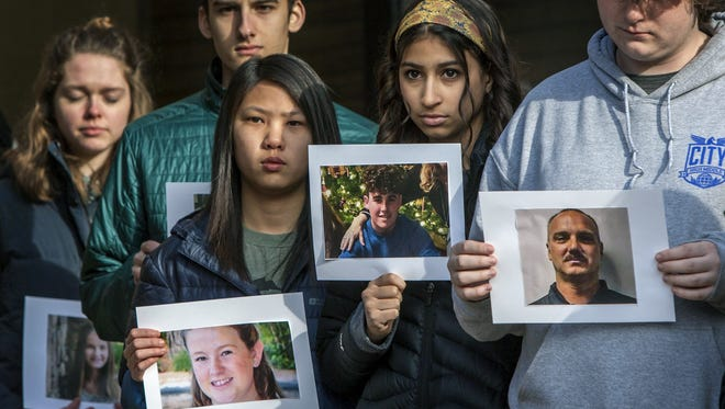 Students from City High Middle School in Grand Rapids hold pictures of victims killed in the Marjory Stoneman Douglas High School shooting in Parkland, Fla., as they take part in a national school walkout to protest gun violence, Wednesday, March 14, 2018. (Cory Morse /The Grand Rapids Press via AP)