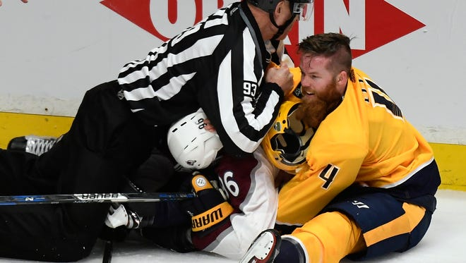 Linesman Brian Murphy tries to break up a fight between Predators defenseman Ryan Ellis (4), another Preds player and Avalanche right wing Mikko Rantanen (96) during the second period in game 2 of the first round NHL Stanley Cup Playoffs at Bridgestone Arena Saturday, April 14, 2018, in Nashville, Tenn.
