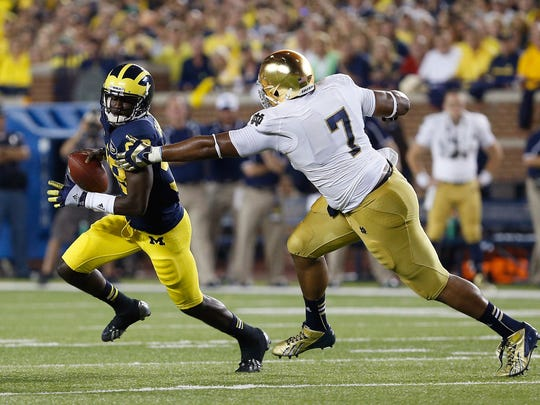 Devin Gardner eludes the reach of Stephon Tuitt during the 2013 game in Ann Arbor, won by Michigan, 41-30.