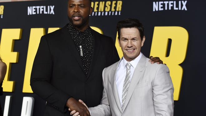 """Winston Duke, left, and Mark Wahlberg star in the Netflix film """"Spenser Confidential,"""" one of Netflix's most popular original movies. The two pose together at the world premiere of the film at the Regency Village Theatre on Feb. 27, 2020, in Los Angeles."""