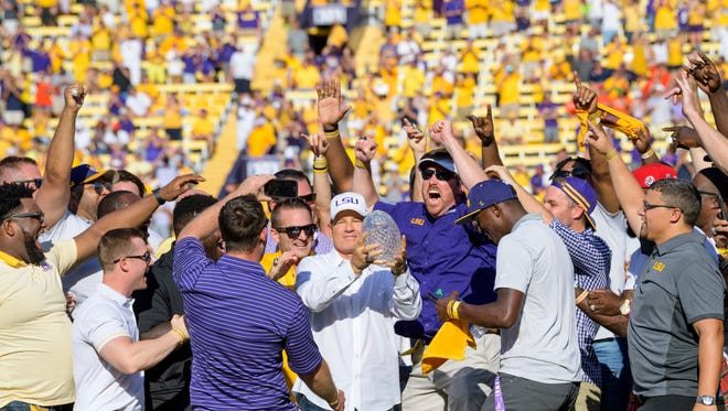 Former LSU head coach Les Miles, center, is mobbed by LSU football alumni of the 2007-8 BCS National Championship team during a halftime ceremony in an NCAA college football game against Auburn in Baton Rouge, La., Saturday, Oct. 14, 2017. (AP Photo/Matthew Hinton)